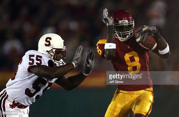 Wide receiver Dwayne Jarrett of the USC Trojans is pushed out of bounds by Michael Okwo of the Stanford Cardinal following a reception during the...
