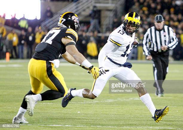 Wide receiver Eddie McDoom of the Michigan Wolverines rushes up field during the second quarter against defensive back Brandon Snyder of the Iowa...