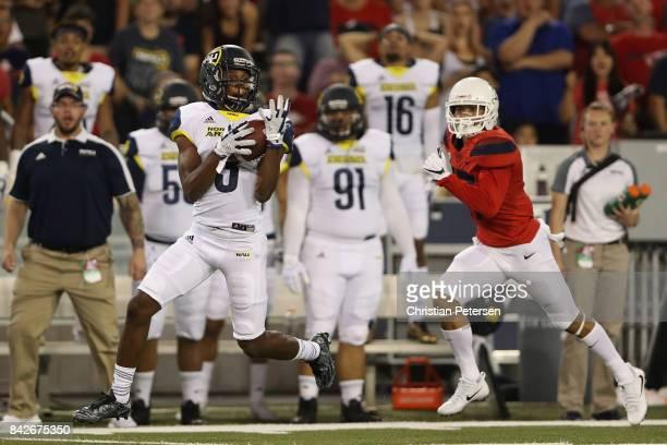 Wide receiver Elijah Marks of the Northern Arizona Lumberjacks catches a 45 yard reception past cornerback Jace Whittaker of the Arizona Wildcats...