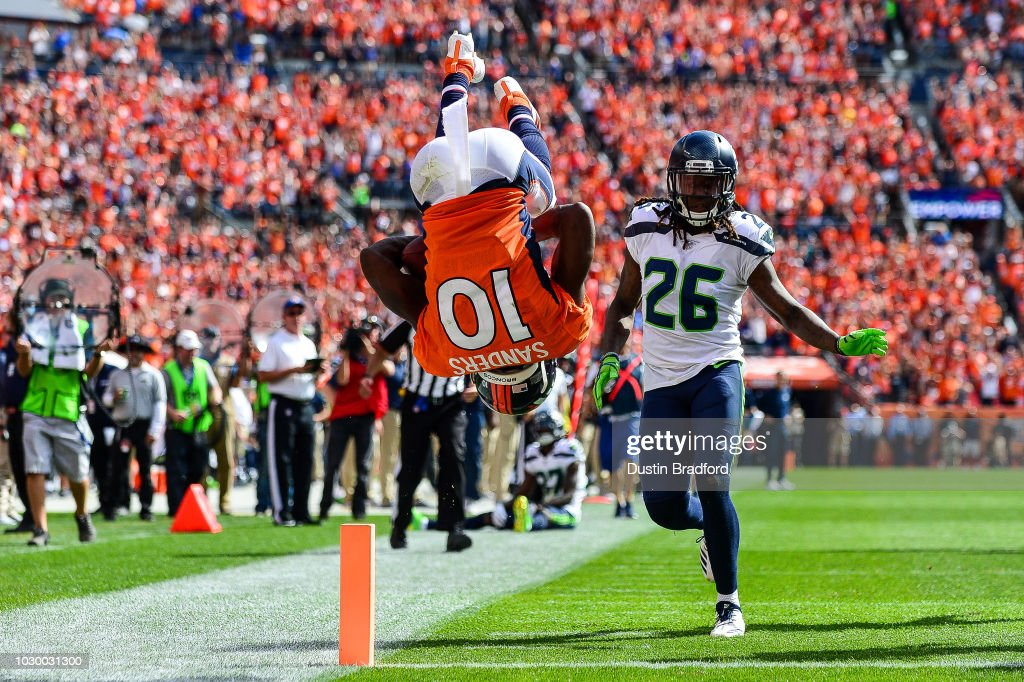 Wide receiver Emmanuel Sanders #10 of the Denver Broncos does a somersault into the end zone with a second quarter touchdown under coverage by cornerback Shaquill Griffin #26 of the Seattle Seahawks during a game at Broncos Stadium at Mile High on September 9, 2018 in Denver, Colorado.
