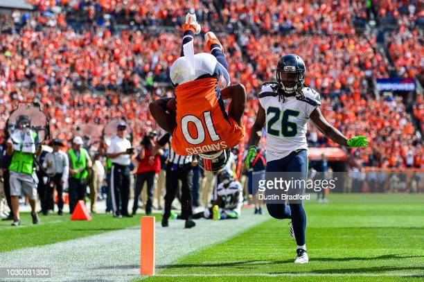 Wide receiver Emmanuel Sanders of the Denver Broncos does a somersault into the end zone with a second quarter touchdown under coverage by cornerback...