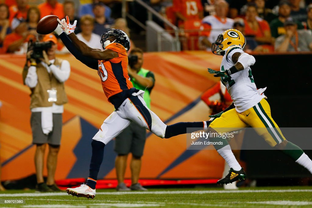 Wide receiver Emmanuel Sanders #10 of the Denver Broncos drops a pass while covered by cornerback Quinten Rollins #24 of the Green Bay Packers in the second quarter of a Preseason game at Sports Authority Field at Mile High on August 26, 2017 in Denver, Colorado.