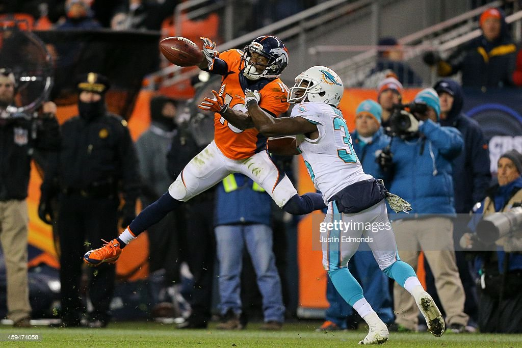 Wide receiver Emmanuel Sanders #10 of the Denver Broncos has a fourth quarter reception for a first down under coverage by cornerback Walt Aikens #35 of the Miami Dolphins at Sports Authority Field at Mile High on November 23, 2014 in Denver, Colorado.