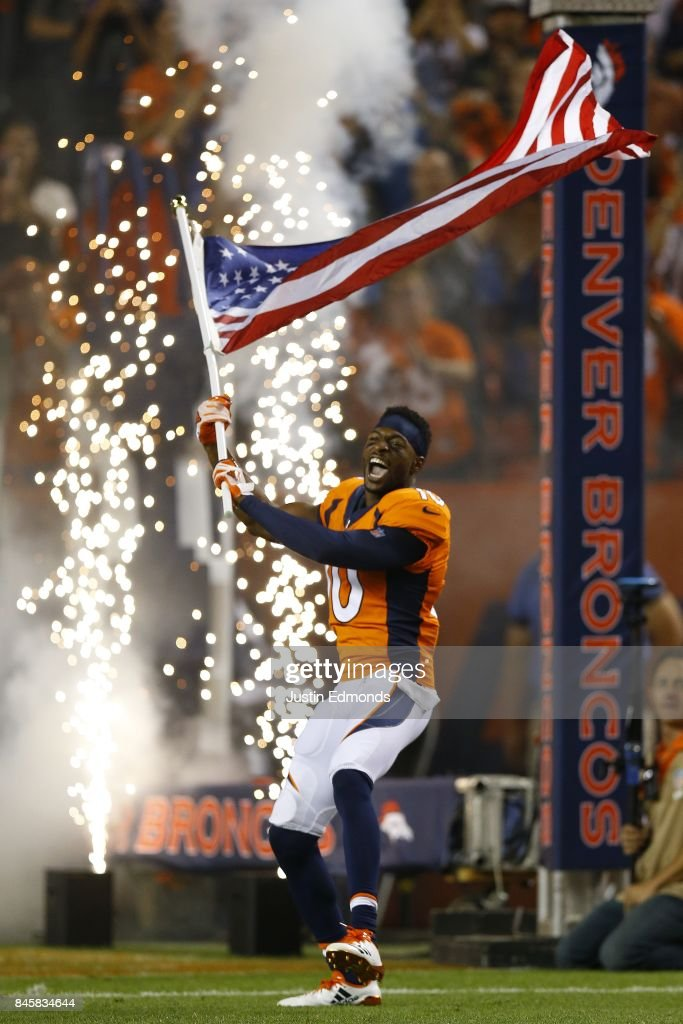 Wide receiver Emmanuel Sanders #10 of the Denver Broncos is introduced to the game while carrying the American Flag at Sports Authority Field at Mile High on September 11, 2017 in Denver, Colorado.