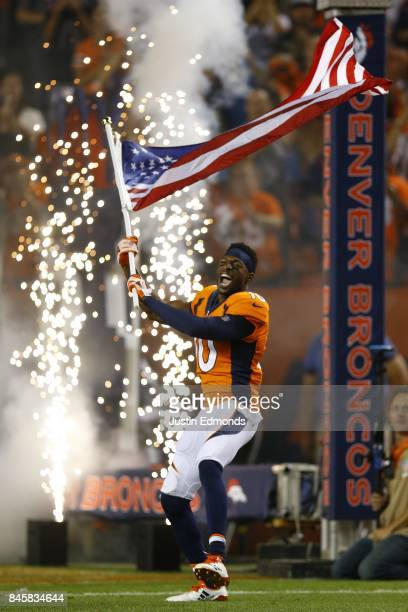 Wide receiver Emmanuel Sanders of the Denver Broncos is introduced to the game while carrying the American Flag at Sports Authority Field at Mile...