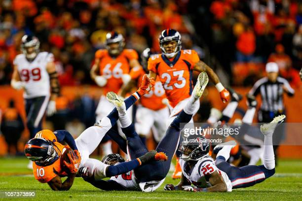 Wide receiver Emmanuel Sanders of the Denver Broncos is tackled by strong safety Justin Reid and strong safety Kareem Jackson of the Houston Texans...