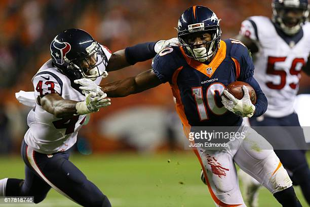Wide receiver Emmanuel Sanders of the Denver Broncos stiff arms defensive back Corey Moore of the Houston Texans in the second quarter of the game at...