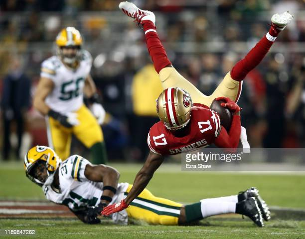 Wide receiver Emmanuel Sanders of the San Francisco 49ers is upended by strong safety Adrian Amos of the Green Bay Packers after making a catch...