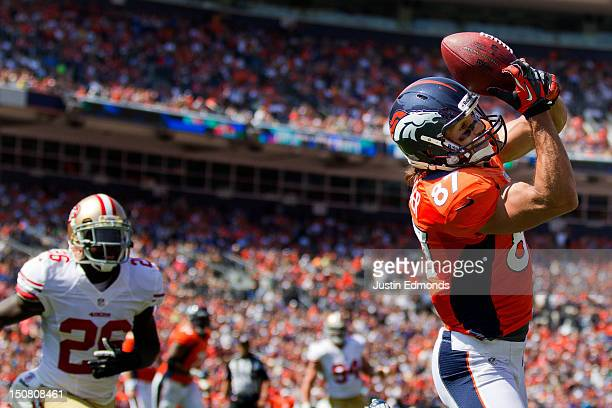 Wide receiver Eric Decker of the Denver Broncos makes a catch for a touchdown as cornerback Tramaine Brock of the San Francisco 49ers looks on during...