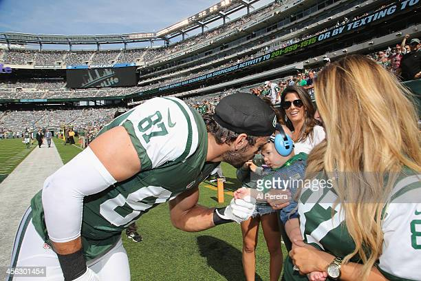 Wide Receiver Eric Decker of the New York Jets visits with his wife, Jessie James Decker and their baby when she attends the Detroit Lions vs New...