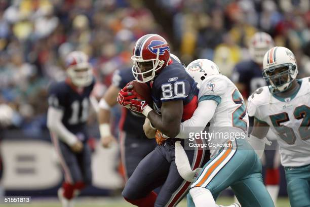 Wide receiver Eric Moulds of the Buffalo Bills is tackled by cornerback Patrick Surtain of the Miami Dolphins on October 17 2004 at Ralph Wilson...