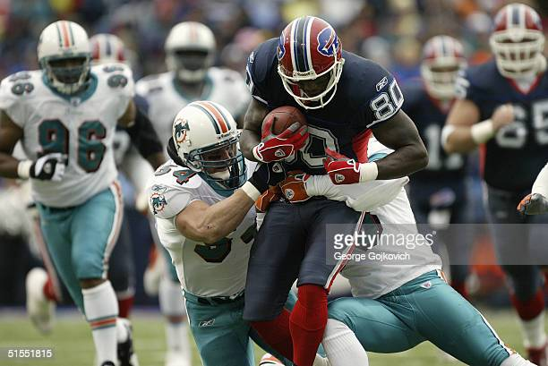 Wide receiver Eric Moulds of the Buffalo Bills is tackled by linebacker Zach Thomas and cornerback Patrick Surtain of the Miami Dolphins on October...