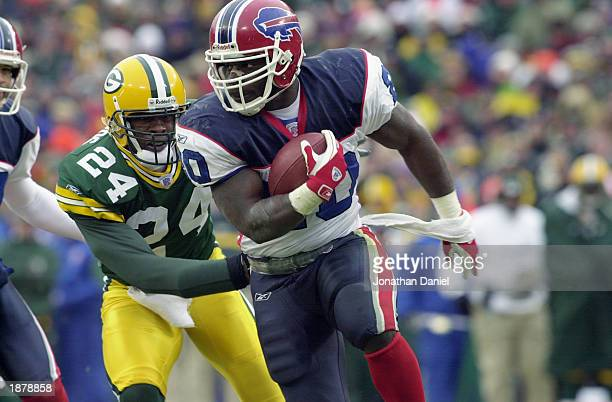Wide receiver Eric Moulds of the Buffalo Bills runs the ball as Antuan Edwards of the Green Bay Packers pursues during the game at Lambeau Field on...