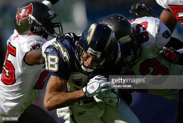 Wide receiver Eric Parker of the San Diego Chargers gets hit by linebacker Shelton Quarles and cornerback Brian Kelly of the Tampa Bay Buccaneers...