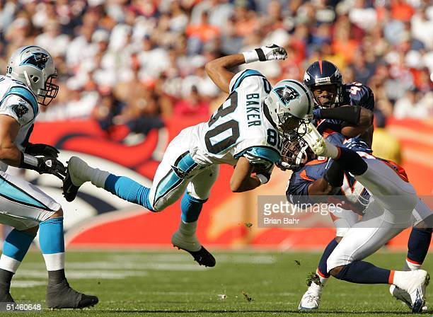 Wide receiver Eugene Baker of the Carolina Panthers gets upended by safety Nick Ferguson of the Denver Broncos and cornerback Roc Alexander of the...