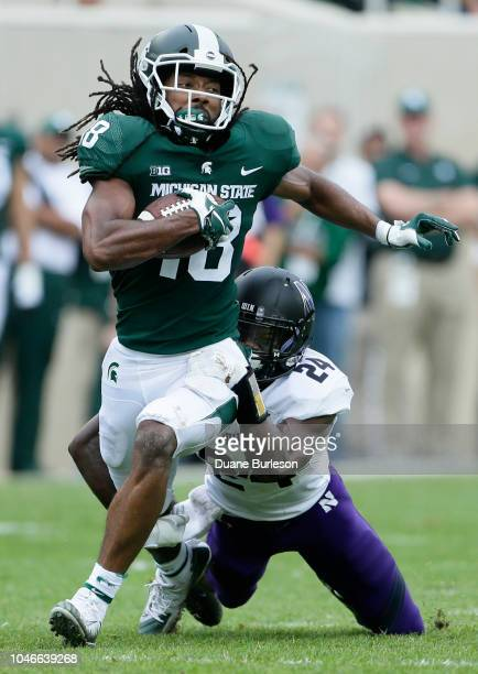 Wide receiver Felton Davis III of the Michigan State Spartans is tackled by cornerback Montre Hartage of the Northwestern Wildcats after a first down...