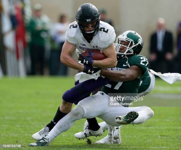 Wide receiver Flynn Nagel of the Northwestern Wildcats is tackled by safety Khari Willis of the Michigan State Spartans during the second half at...