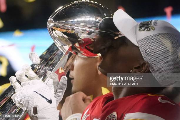 Wide receiver for the Kansas City Chiefs Mecole Hardman kisses the Vince Lombardi Trophy as he celebrates with teammates on the podium after winning...