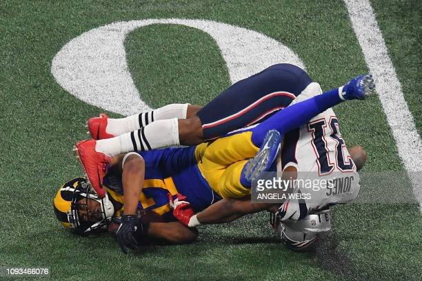 TOPSHOT Wide receiver for the Los Angeles Rams Robert Woods is tackled by Jonathan Jones of the New England Patriots during Super Bowl LIII between...