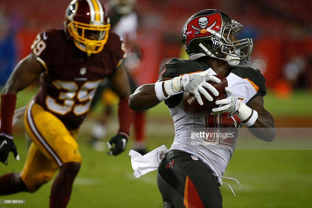 Wide receiver Freddie Martino #16 of the Tampa Bay Buccaneers hauls in a pass from quarterback Ryan Griffin for a first down while being pressured by running back Keith Marshall #39 of the Washington Redskins during the fourth quarter of an NFL preseason game on August 31, 2016 at Raymond James Stadium in Tampa, Florida.