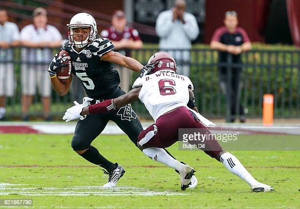 Wide receiver Gabe Myles of the Mississippi State Bulldogs tries to get past defensive back Donovan Wilson of the Texas AM Aggies as he carries the...