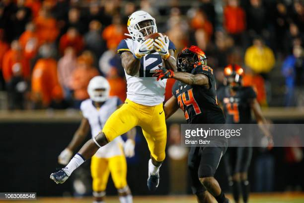 Wide receiver Gary Jennings Jr #12 of the West Virginia Mountaineers makes a catch over safety Jarrick Bernard of the Oklahoma State Cowboys in the...
