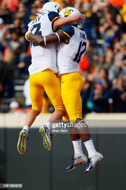 Wide receiver Gary Jennings Jr #12 of the West Virginia Mountaineers celebrates a 13yard touchdown run with wide receiver David Sills V against the...