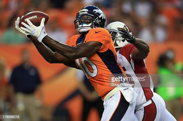 Wide receiver Gerell Robinson of the Denver Broncos makes a 45 yard pass reception against the defense of cornerback Javier Arenas of the Arizona...