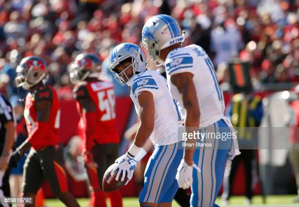 Wide receiver Golden Tate of the Detroit Lions pretends to putt a golfball in front of wide receiver Marvin Jones as he celebrates in the end zone...