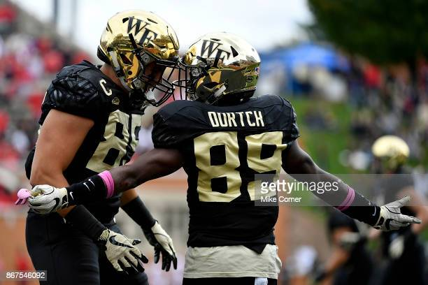 Wide receiver Greg Dortch celebrates with tight end Cam Serigne of the Wake Forest Demon Deacons after scoring a touchdown against the Louisville...