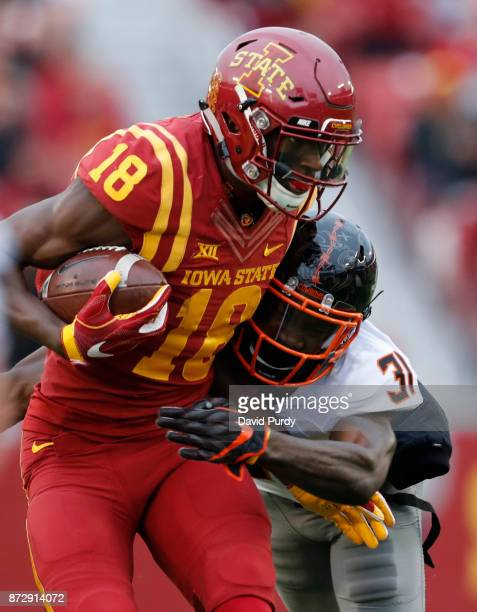 Wide receiver Hakeem Butler of the Iowa State Cyclones is tackled by safety Tre Flowers of the Oklahoma State Cowboys as he rushed for yards in the...