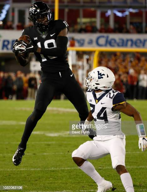 Wide receiver Hakeem Butler of the Iowa State Cyclones pulls in a pass as cornerback Hakeem Bailey of the West Virginia Mountaineers defends in the...