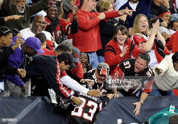 Wide receiver Harry Douglas of the Atlanta Falcons celebrates a touchdown return against the Carolina Panthers with fans at the Georgia Dome on...