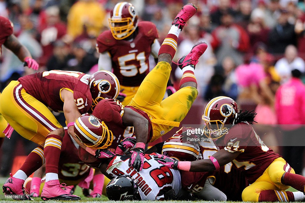 Wide receiver Harry Douglas #83 of the Atlanta Falcons is hit by multiple Washington Redskins defenders in the second quarter at FedExField on October 7, 2012 in Landover, Maryland.