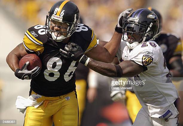 Wide receiver Heinz Ward of the Pittsburgh Steelers pushes away from the tackle attempt of safety Ed Reed of the Baltimore Ravens on September 7 2003...