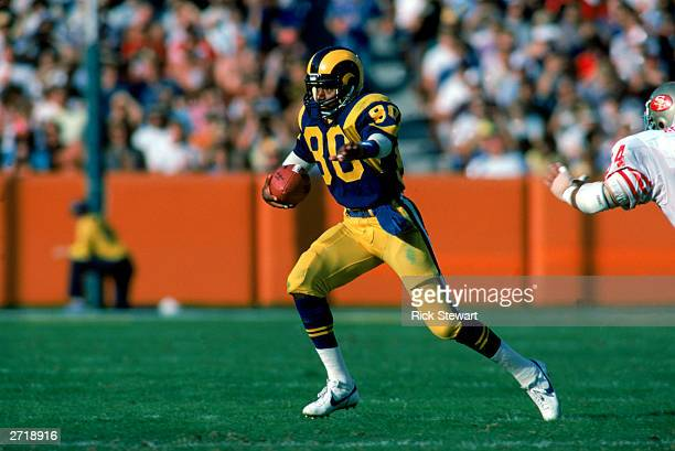 Wide receiver Henry Ellard of the Los Angeles Rams carries the ball down an open field during a 1984 NFL game.