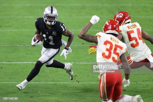 Wide receiver Henry Ruggs III of the Las Vegas Raiders runs with the ball after a pass reception as cornerback Charvarius Ward and outside linebacker...