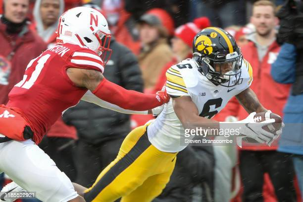 Wide receiver Ihmir SmithMarsette of the Iowa Hawkeyes dives into the end zone ahead of the tackle from cornerback Lamar Jackson of the Nebraska...