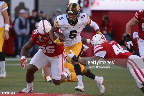 Wide receiver Ihmir SmithMarsette of the Iowa Hawkeyes runs from defensive lineman Carlos Davis of the Nebraska Cornhuskers and defensive back Joshua...