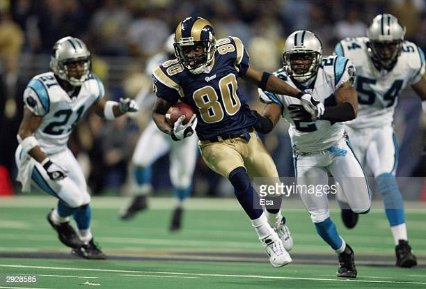 Wide receiver Isaac Bruce of the St. Louis Rams attempts to break free from cornerback Ricky Manning Jr. #24 of the Carolina Panthers during the NFC...
