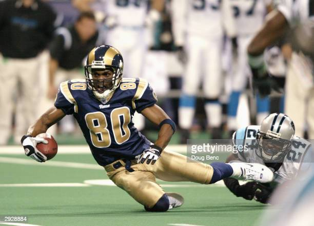 Wide receiver Isaac Bruce of the St. Louis Rams is tripped up by cornerback Ricky Manning Jr. #24 of the Carolina Panthers during the NFC Divisional...