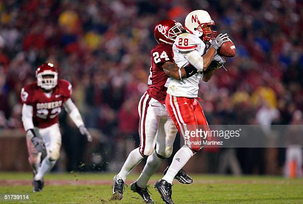 Wide receiver Isaiah Fluellen of the Nebraska Cornhuskers catches a pass against cornerback Marcus Walker of the Oklahoma Sooners on November 13 2004...
