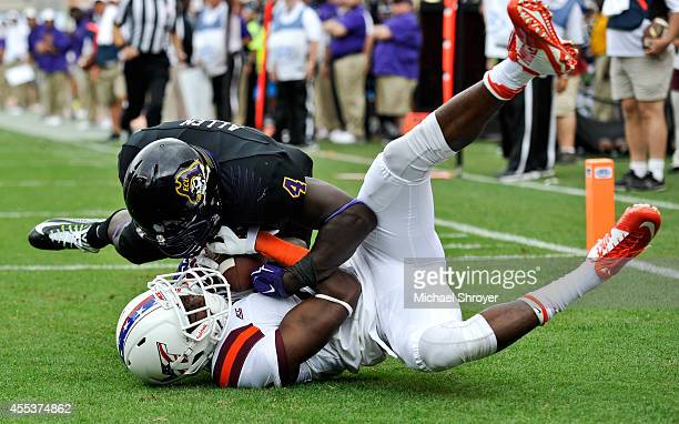 Wide receiver Isaiah Ford of the Virginia Tech Hokies makes a catch in the end zone for a touchdown while being defended by defensive back Detric...