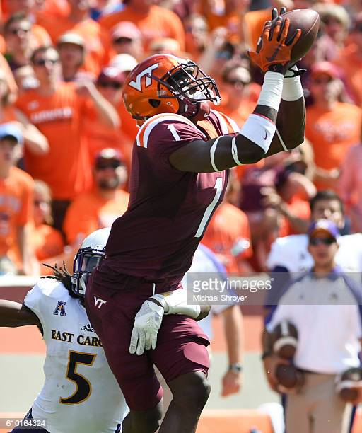 Wide receiver Isaiah Ford of the Virginia Tech Hokies makes a catch while being defended by defensive back Corey Seargent of the East Carolina...