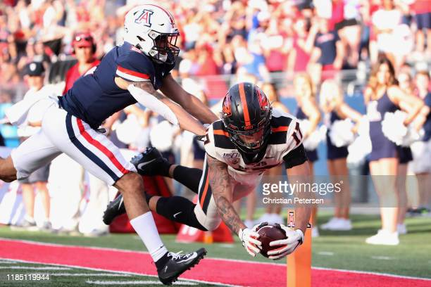Wide receiver Isaiah Hodgins of the Oregon State Beavers dives into the end zone to score on a 25-yard touchdown reception past cornerback Lorenzo...