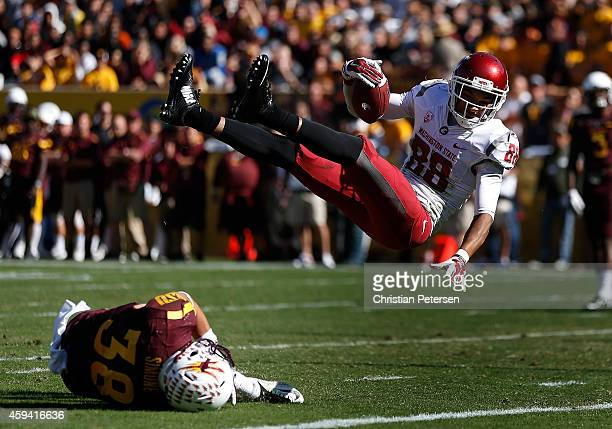 Wide receiver Isiah Myers of the Washington State Cougars flips into the end zone over defensive back Jordan Simone of the Arizona State Sun Devils...