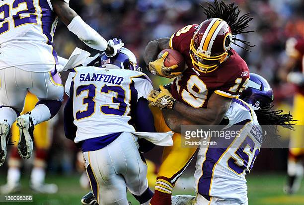 Wide receiver Jabar Gaffney of the Washington Redskins is hit by safety Jamarca Sanford of the Minnesota Vikings and Erin Henderson in the second...