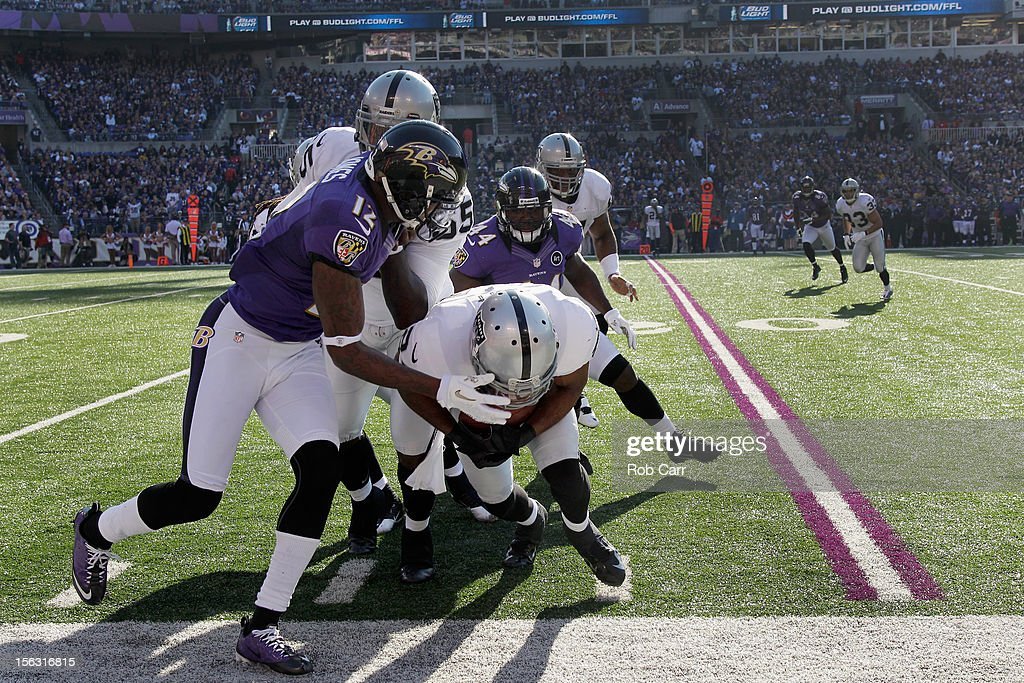 Wide receiver Jacoby Ford #12 of the Oakland Raiders pushes cornerback Michael Huff #24 of the Oakland Raiders out of bounds after Huff recovered a fumble during the first half at M&T Bank Stadium on November 11, 2012 in Baltimore, Maryland.