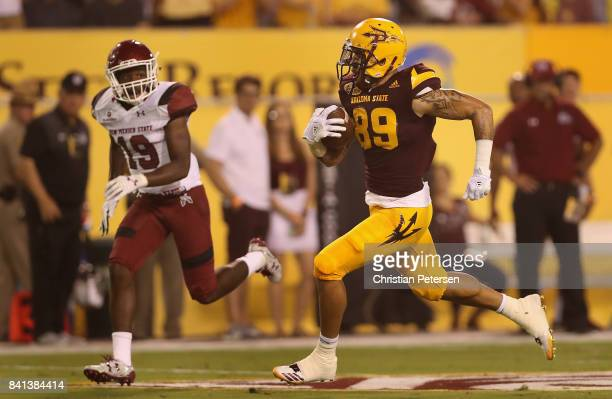 Wide receiver Jalen Harvey of the Arizona State Sun Devils runs with the football en route to scoring on a 53 yard touchdown reception past defensive...