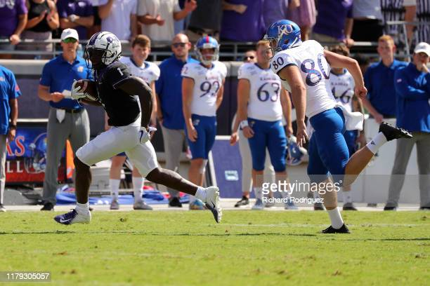 Wide receiver Jalen Reagor of the TCU Horned Frogs is pursued by punter Kyle Thompson of the Kansas Jayhawks as Reagor returns a punt for a touchdo...